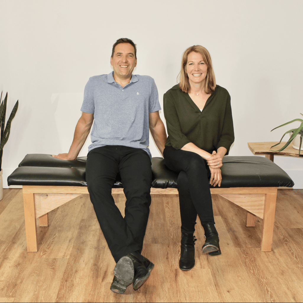 Dr Laina & Dr Jamie sitting on Chiropractic table smiling in London Ontario